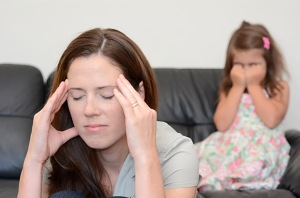 stressed-parent-in-front-of-crying-child-on-couch-017a-depressive-symptoms-in-parents